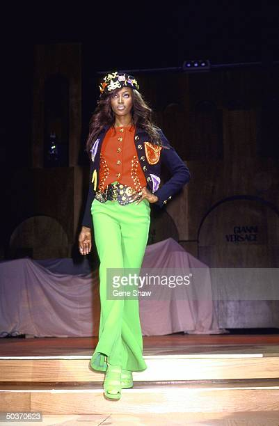 British model Naomi Campbell on a runway dressed in green bellbottom pants an oversized belt a red shirt with gold buttons and accents and a short...