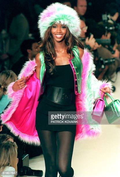 British model Naomi Campbell presents this fake fur jacket in pink and green over matching leatherlike vests a stretch black minidress and leather...