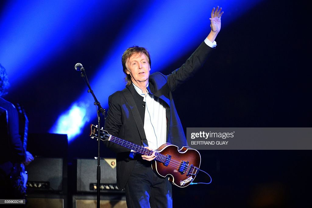 British musician and former Beatles' member Paul McCartney performs on stage at the Bercy stadium in Paris on May 30, 2016. / AFP / BERTRAND