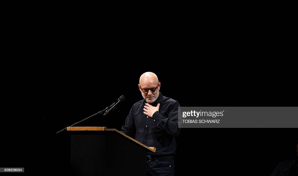 British musician, composer and visual artist Brian Eno pauses during his speech at an event to mark the official launch of the Democracy in Europe Movement 2025 (DiEM25) in Berlin on February 9, 2016. Greece's far-left former finance minister Yanis Varoufakis and supporters came to Berlin to launch a pan-European grassroots political movement, saying its goal was to 'democratise' the 28-member bloc. / AFP / TOBIAS SCHWARZ