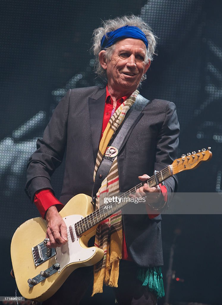British musician Keith Richards of the Rolling Stones performs on the Pyramid Stage on the fourth day of the Glastonbury Festival of Contemporary Performing Arts near Glastonbury, southwest England, on June 29, 2013. The festival attracts 170,000 party-goers to the dairy farm in Somerset, and this year's tickets sold out within two hours of going on sale. The Rolling Stones are will perform at the festival for the first time.