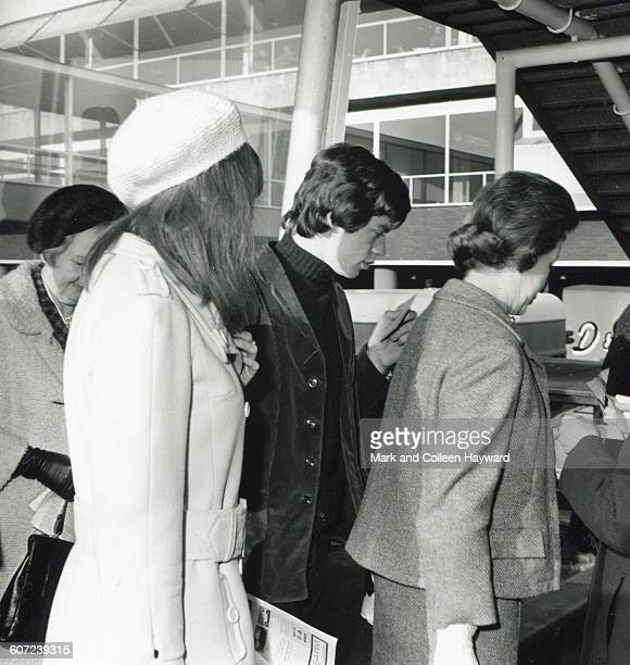 British musician Mick Jagger of the group the Rolling Stones carries a ticket as he stands in a queue April 27 1964