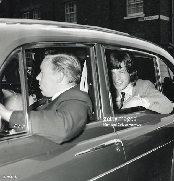 British musician Mick Jagger of the group the Rolling Stones smiles from the backseat of a car as he is driven away after leaving jail on drug...