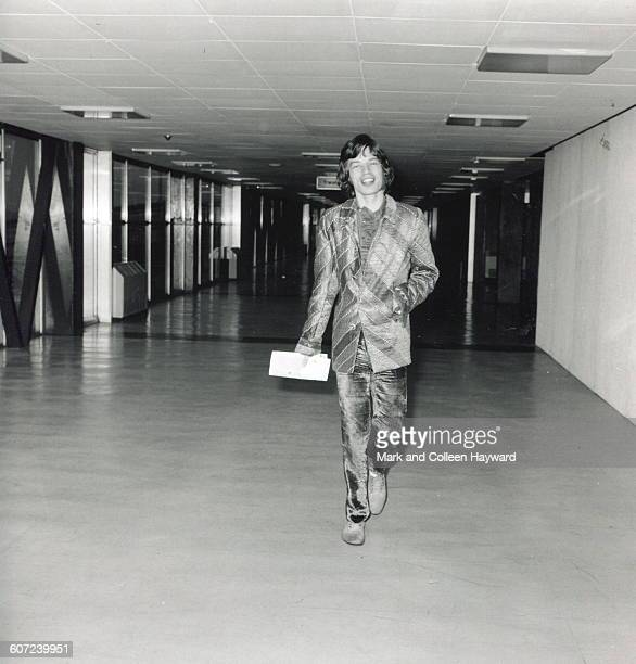 British musician Mick Jagger of the group the Rolling Stones walks through an unidentified airport 1971