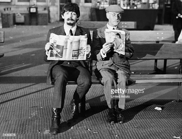 British musician Paul McCartney and British actor Wilfred Brambell sit on a bench holding a newspaper and a magazine in a still from the film 'A Hard...