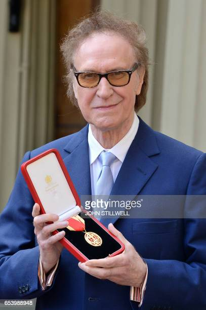 British musician Ray Davies of the sixties group The Kinks poses with his medal after he was knighted for services to music during an investiture...