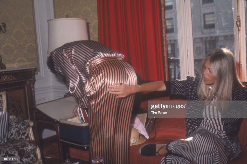 British musician Rod Stewart looks for something in a suitcase as his girlfriend, Swedish actress Britt Ekland, checks out his striped trousers in a hotel room while on a promotional tour in support of Stewart's album 'Atlantic Crossing,' New York, New York, July 29, 1975.