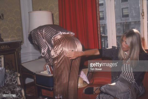 British musician Rod Stewart looks for something in a suitcase as his girlfriend Swedish actress Britt Ekland checks out his striped trousers in a...