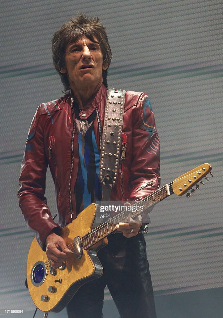 British musician Ron Wood of the Rolling Stones performs on the Pyramid Stage on the fourth day of the Glastonbury Festival of Contemporary Performing Arts near Glastonbury, southwest England, on June 29, 2013. The festival attracts 170,000 party-goers to the dairy farm in Somerset, and this year's tickets sold out within two hours of going on sale. The Rolling Stones are will perform at the festival for the first time. AFP PHOTO/ANDREW COWIE