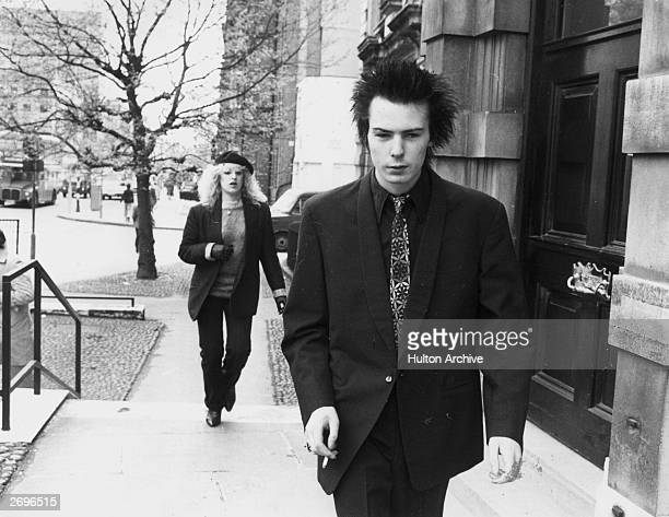 British musician Sid Vicious bass player and vocalist for the British punk rock band The Sex Pistols smokes a cigarette while walking up a flight of...