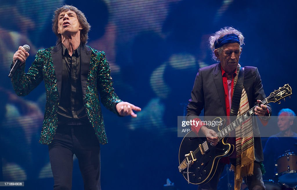 British musicians Mick Jagger (L), Keith Richards (2nd R) and Charlie Watts (R) of the Rolling Stones perform on the Pyramid Stage on the fourth day of the Glastonbury Festival of Contemporary Performing Arts near Glastonbury, southwest England, on June 29, 2013. The festival attracts 170,000 party-goers to the dairy farm in Somerset, and this year's tickets sold out within two hours of going on sale. The Rolling Stones are will perform at the festival for the first time. AFP PHOTO/ANDREW COWIE