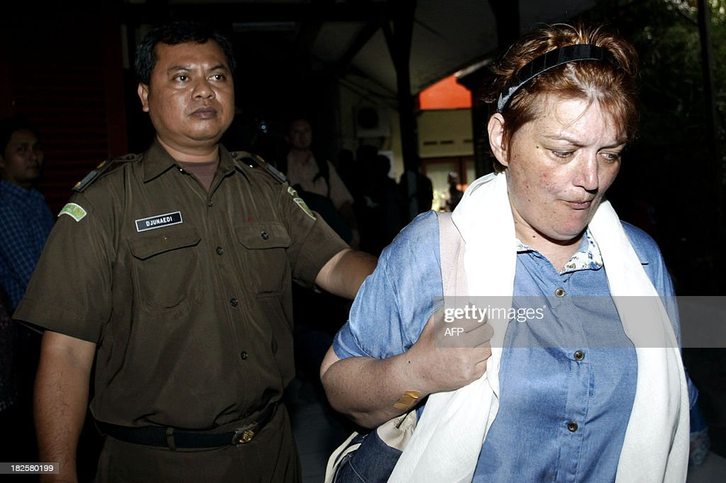 British national Andrea Waldeck (R) is escorted by a court official prior to her trial in Surabaya on October 1, 2013. Waldeck is facing charges of trafficking about 1.5 kilograms (three pounds) of crystal methamphetamine, an offence punishable by death, a prosecutor said. Waldeck, 43 was arrested in late April at a hotel in the city of Surabaya after arriving from China.