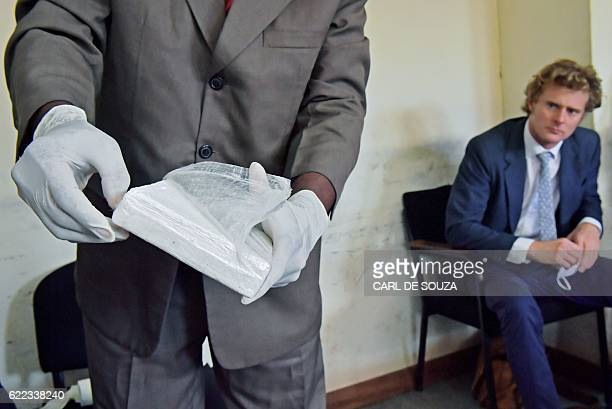 British national Jack Alexander Wolf Marrian who faces charges of trafficking 100 kilos of cocaine from Brazil to the port of Mombasa watches as a...