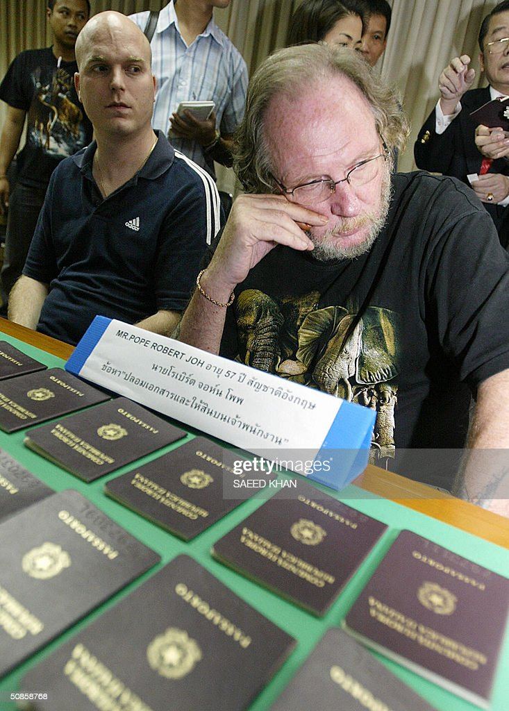British national Robert John Pope (R) and Hofer Philipp of South Africa sit in police custody with fake Italian passpots at an immigration department in Bangkok, 20 May 2004. Two Europeans and a South African have been arrested in the Thai capital for allegedly forging hundreds of Italian passports and visa seals they planned to sell in Europe. AFP PHOTO/ Saeed KHAN