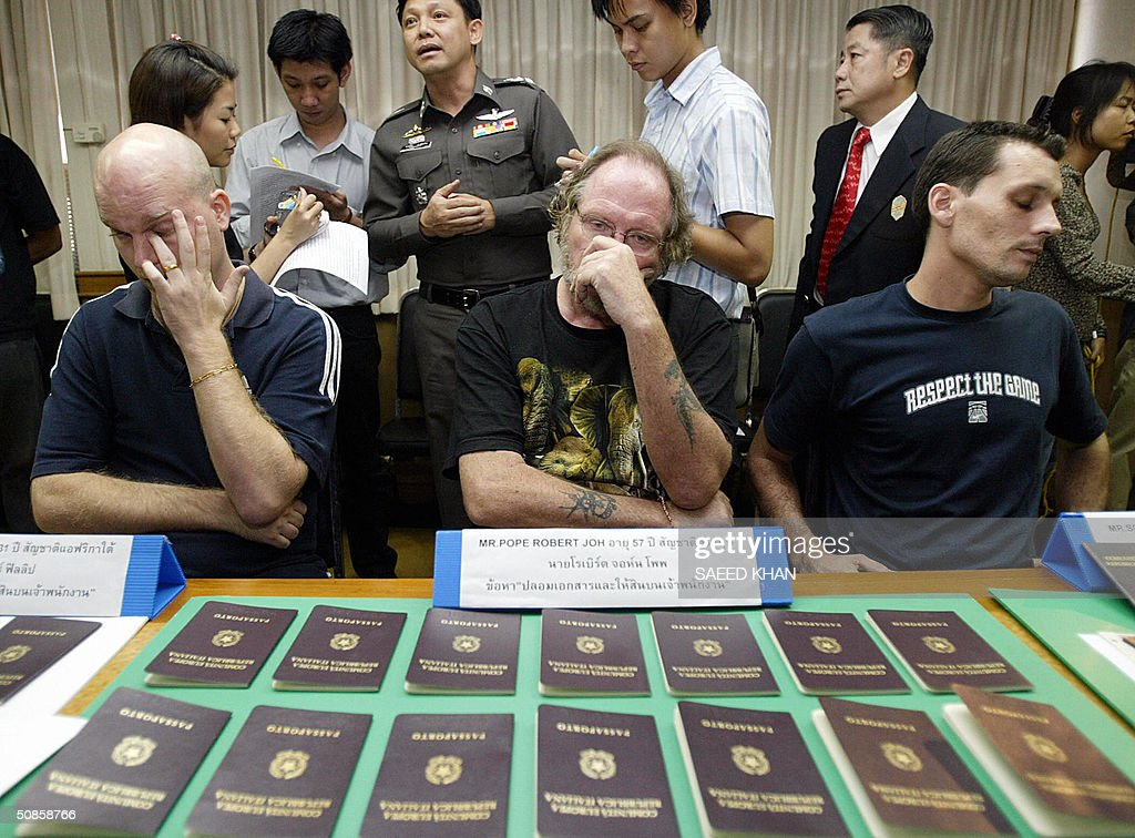 British national Robert John Pope (C) sits in dejection facing fake Italian passports along with his partners Schneider Uwe (R) from Germany and Hofer Philipp of South Africa, in police custody in Bangkok, 20 May 2004. Two Europeans and a South African have been arrested in the Thai capital for allegedly forging hundreds of Italian passports and visa seals they planned to sell in Europe. AFP PHOTO/ Saeed KHAN