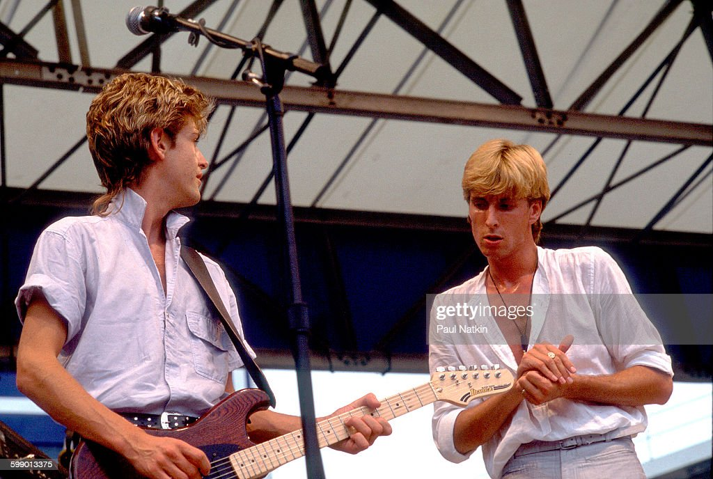 British New Wave musicians Jamie WestOram and Cy Curnin both of the Fixx perform onstage at Comiskey Park Chicago Illinois July 23 1983