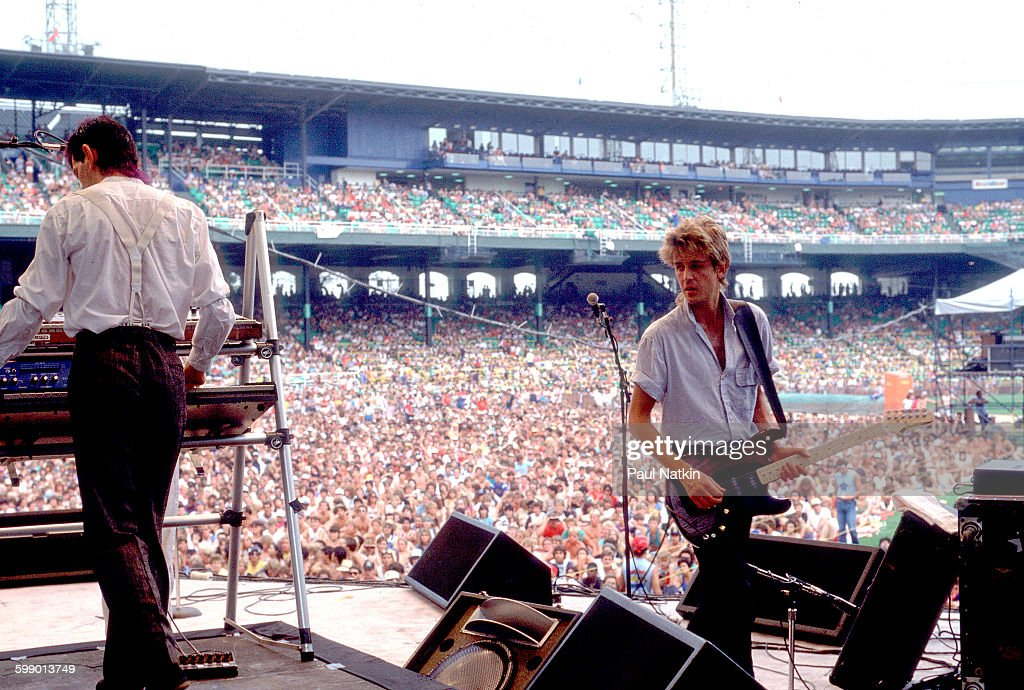 British New Wave musicians Rupert Greenall and Jamie WestOram both of the Fixx perform onstage at Comiskey Park Chicago Illinois July 23 1983