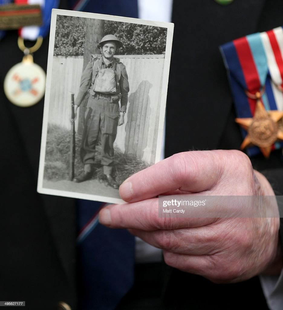 British Normandy Veteran John Ainsworth, 93, who was in the Royal Artillery poses for a photograph holding a photograph of himself in 1940, as he attends a function in the village of Thury-Harcourt on June 4, 2014 near Caen in Normandy, France. Friday 6th June is the 70th anniversary of the D-Day landings which saw 156,000 troops from the allied countries including the United Kingdom and the United States join forces to launch an audacious attack on the beaches of Normandy, these assaults are credited with the eventual defeat of Nazi Germany. A series of events commemorating the 70th anniversary are planned for the week with many heads of state travelling to the famous beaches to pay their respects to those who lost their lives.