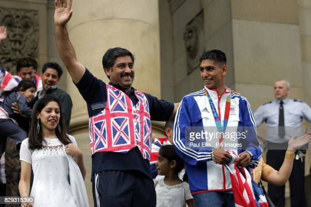 British Olympic silver medal winning boxer Amir Khan with father Shajaad on the steps of the Town Hall during an opentop bus tour of his home town of...