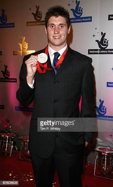 British Olympic silver medalist in open water swimming David Davies poses with his medal on arriving at The National Lottery Awards the annual search...