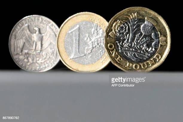 A British one pound sterling coin a one euro coin and a US quarter dollar coin are arranged and photographed in central London on October 5 2017 The...