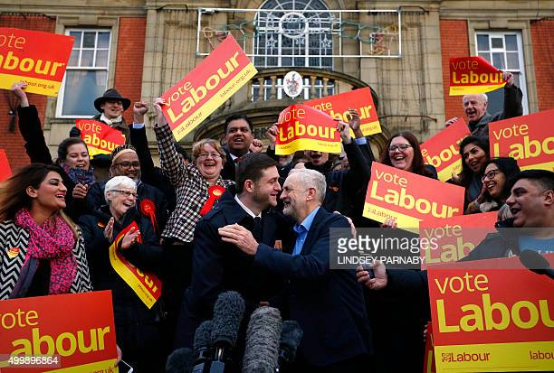 British opposition Labour Party leader Jeremy Corbyn embraces newly elected member of parliament for Oldham West and Royton Jim McMahon outside...