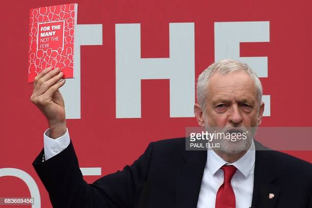 British opposition Labour party leader Jeremy Corbyn holds up his party's manifesto document at the Labour election manifesto launch in Bradford on...