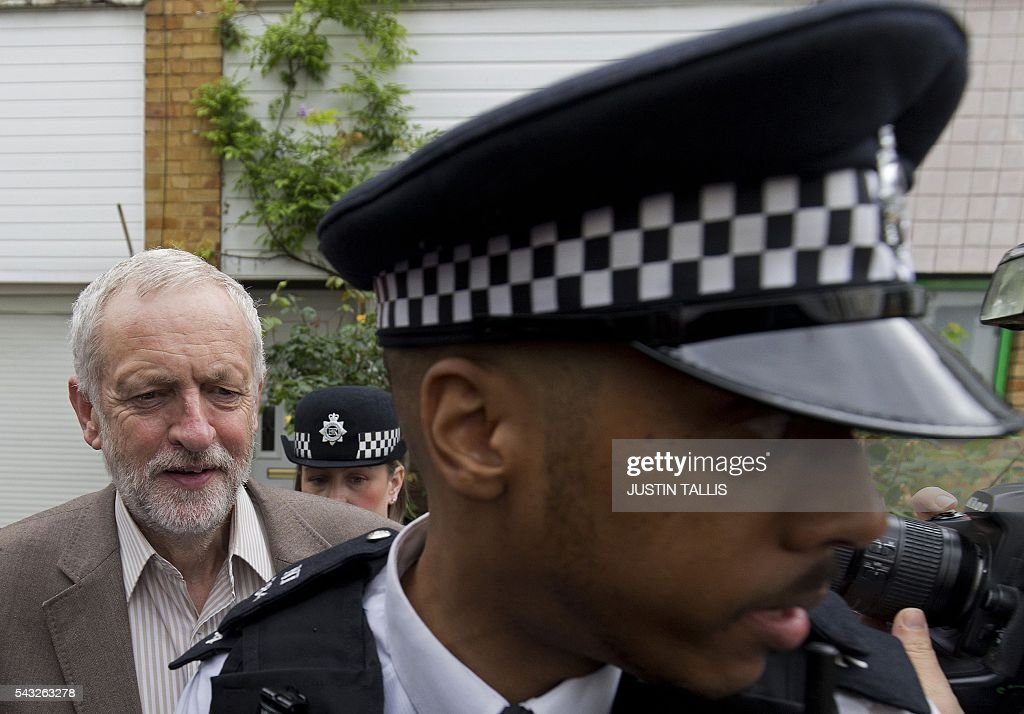 British opposition Labour Party Leader Jeremy Corbyn (L) is escorted by police as he leaves his home in London on June 27, 2016. Britain's opposition leader Jeremy Corbyn insisted he would not give up his job in a Labour Party revolt over his handling of the EU referendum campaign, as the aftershocks from the 'Leave' vote reverberate around the country. / AFP / JUSTIN