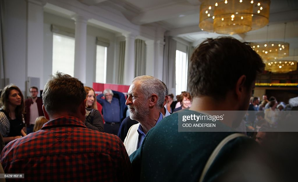 British opposition Labour Party leader Jeremy Corbyn (C) mingles with suuporters after delivering a speech following the pro-Brexit result of the UK's EU referendum vote, in central London on June 25, 2016. The result of Britain's June 23 referendum vote to leave the European Union (EU) has pitted parents against children, cities against rural areas, north against south and university graduates against those with fewer qualifications. London, Scotland and Northern Ireland voted to remain in the EU but Wales and large swathes of England, particularly former industrial hubs in the north with many disaffected workers, backed a Brexit. / AFP / ODD