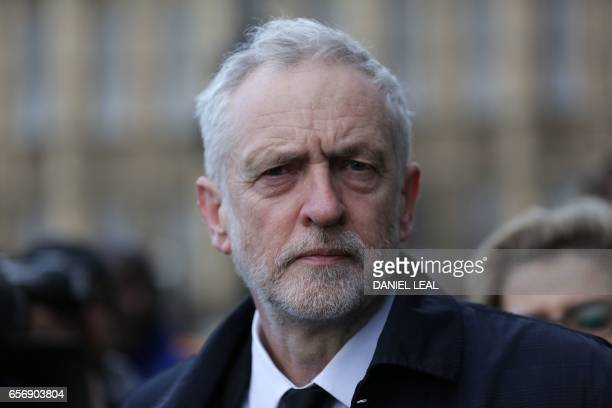 British Opposition Labour Party leader Jeremy Corbyn walks along Westminster Bridge by the Houses of Parliament in central London on March 23 2017...