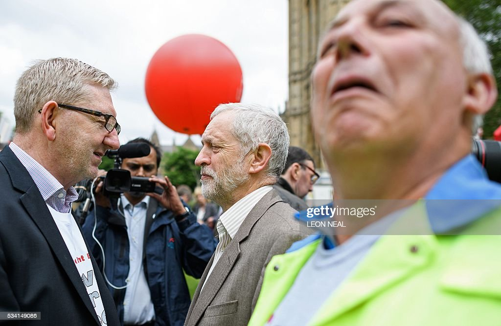 British oppostion Labour Party leader Jeremy Corbyn (C), reacts as he stands with Unite union General Secretary Len McCluskey (L), as they join steel workers following a march through central London on May 25, 2016. Britain's business minister Sajid Javid met Tata Steel bosses in Mumbai ahead of a crunch board meeting on Wednesday expected to discuss potential buyers for its loss-making UK assets. Tata Steel, Britain's biggest steel employer, announced in March that it planned to sell its Port Talbot plant in Wales and other assets, putting 15,000 jobs at risk. / AFP / LEON