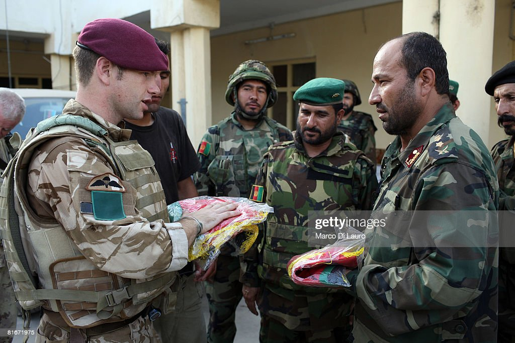 British paratrooper from 3rd Battalion The Parachute Regiment, A Company Commander Maj. Matthew Cansdale, 33, from Winchester, England, gives to an Afghan National Army Officer same Afghan flags as a gift during a visit to an Afghan National Army (ANA) compound to hand over the Kandahar football stadium to the Afghan security forces on June 22, 2008 in Kandahar, Afghanistan. British Paratroopers conducted operation 'Daor Bukhou' by flying in hundreds of paratroopers from 3rd Battalion The Parachute Regiment into the football stadium of Kandahar City for the first time since 2001 to provide a presence in the city to support the Afghan National Security Forces in their battle against the Taliban. The regiment was retrieved from the base on June 22, 2008 upon completion of its mission.