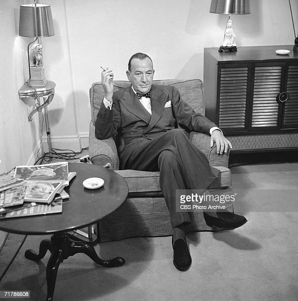 British performer and composer Noel Coward sits at home with his legs crossed and smokes a cigarette before an appearance on the CBS television show...