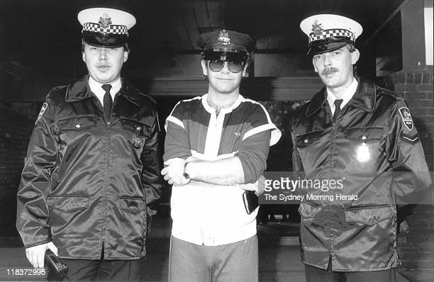 British performer Elton John is escorted by two New South Wales police officers after he arrives at Sydney Airport wearing a New York police hat...