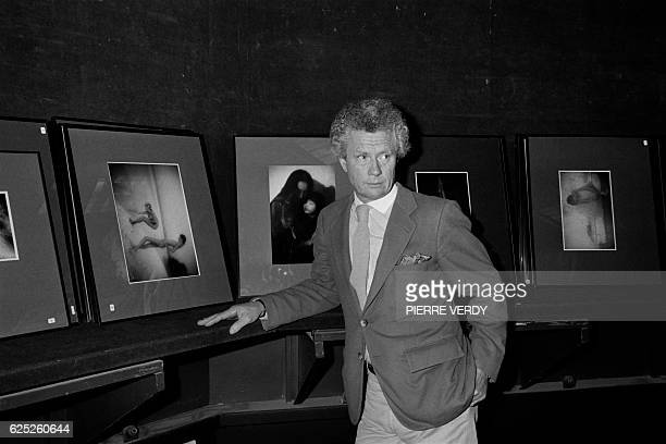 British photographer and film director David Hamilton poses on November 19 1983 in front of his work during a sale of his photos at the auction house...