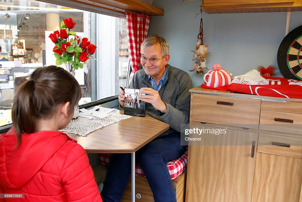British photographer <a gi-track='captionPersonalityLinkClicked' href=/galleries/search?phrase=Martin+Parr&family=editorial&specificpeople=4387023 ng-click='$event.stopPropagation()'>Martin Parr</a> signs his book 'Real Food' in his 'booktruck' on May 24, 2016 in Paris, France.