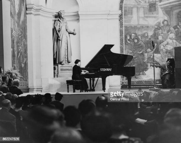 British pianist Dame Myra Hess entertains workers during their lunchtime at the Royal Exchange London World War II 30th June 1942