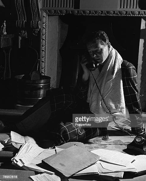 British Playwright Terrence Rattigan sits on the floor by the fireside making a late night telephone call while working on a script Rattigan is...