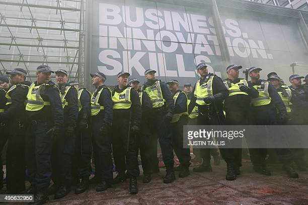 British police are seen through smoke from a smoke flare manning a cordon during scuffles with a contingent of the annual demonstration against...