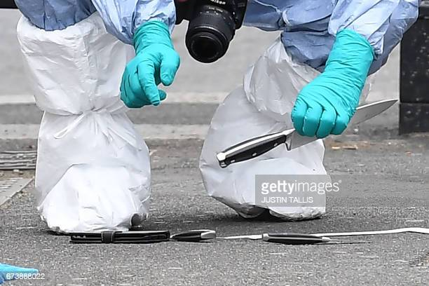 A British police forensics officer holds a knife as he collects evidence on Whitehall near the Houses of Parliament in central London on April 27 at...