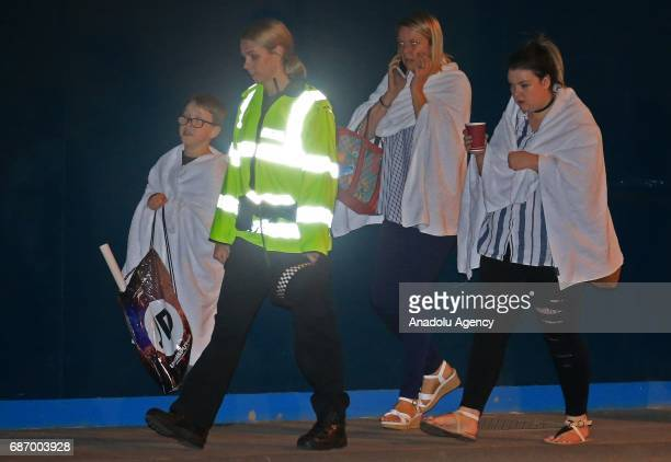 British police officer escorts walking casualties away from the Manchester Arena stadium in Manchester United Kingdom on May 23 2017 A large...