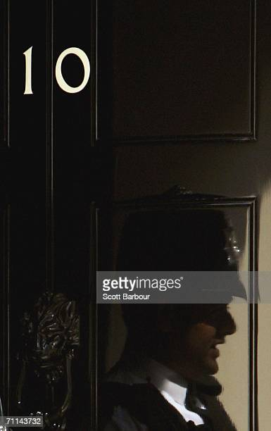 British police officer is reflected in the door of Number 10 before Britain's Prime Minister Tony Blair departs Downing Street to attend Prime...
