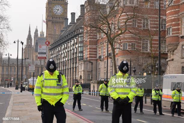 British police officers bow their heads as they stand near a police cordon directly ourside New Scotland Yard and within sight of the Houses of...