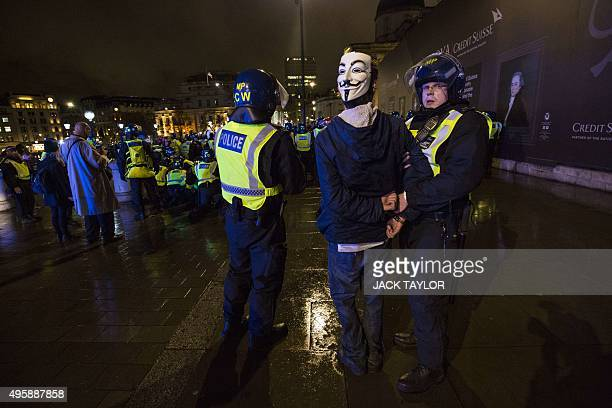 British police officers detain a protester during the 'Million Masks March' organised by the anticapitalist group Anonymous in Trafalgar Square in...