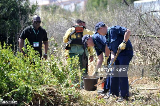 British Police officers dig for evidence during a search of an area of scrubland as part of a new investigation into the disappearance Madeleine...