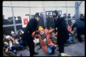 British police officers dragging protestor participating in antinuclear missle demonstration outside Greenham Common Air Base during arrival of US...