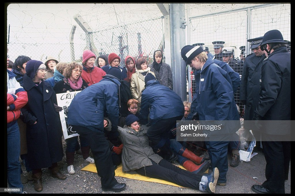 British police officers dragging protestor participating in anti-nuclear missle demonstration outside Greenham Common Air Base during arrival of US Tomahawk cruise missiles.