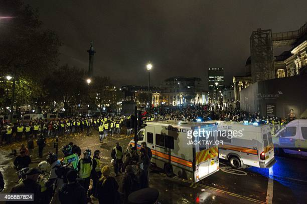 British police officers form a blockade around anticapitalist protesters during the 'Million Masks March' organised by the group Anonymous in...