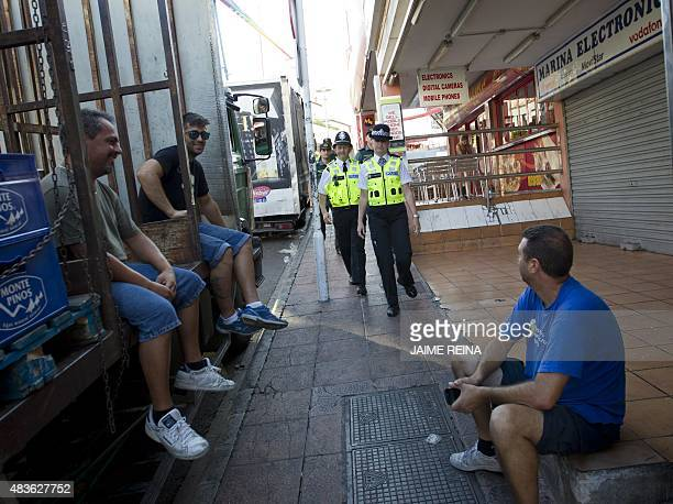 British police officers popularly known as 'bobbies' walk past some men as they patrol with Spanish Civil Guards at Punta Ballena street in the...
