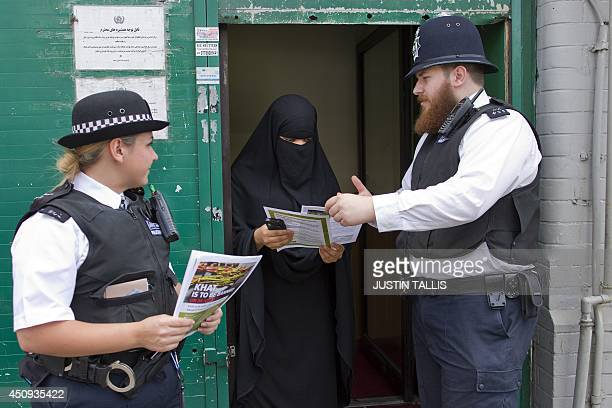 British police officers speak with a woman outside a Mosque about the ban on the stimulant plant Khat which is to be made illegal and classified as a...